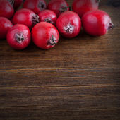 Red hawthorn berries on wooden background — Stock Photo