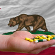 Holding pills in hand in front of california us state flag — Stock Photo #12556866