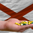 Holding pills in hand in front of alabama us state flag — Stock fotografie