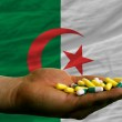 Постер, плакат: Holding pills in hand in front of algeria national flag