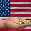 Holding pills in hand in front of america national flag - Stock Photo