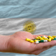 Holding pills in hand in front of argentina national flag - Stock Photo