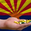 Holding pills in hand in front of arizona us state flag — Stock Photo
