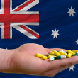 Holding pills in hand in front of australia national flag - Stock Photo