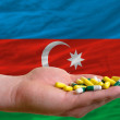 Holding pills in hand in front of azerbaijan national flag - Stock Photo