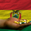 Holding pills in hand in front of bolivia national flag - Stock Photo