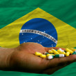 Holding pills in hand in front of brazil national flag - Stock Photo