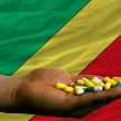 Holding pills in hand in front of congo national flag - Stock Photo