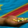 Holding pills in hand in front of congo national flag — Foto Stock