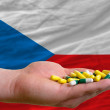 Holding pills in hand in front of czech national flag - Stock Photo