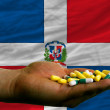 Holding pills in hand in front of dominican national flag - Stock Photo