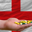 Stock Photo: Holding pills in hand in front of england national flag