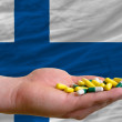 Stock Photo: Holding pills in hand in front of finland national flag