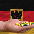 Stock Photo: Holding pills in hand in front of germany national flag