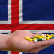 Stock Photo: Holding pills in hand in front of iceland national flag