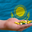 Holding pills in hand in front of kazakhstnational flag — Stock Photo #12558827