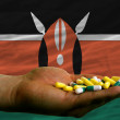 Holding pills in hand in front of kenya national flag — Stock Photo
