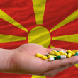Stock Photo: Holding pills in hand in front of macedoninational flag