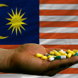 Stock Photo: Holding pills in hand in front of malaysinational flag