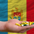 Stock Photo: Holding pills in hand in front of moldovnational flag