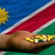 Stock Photo: Holding pills in hand in front of namibinational flag