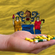 Stock Photo: Holding pills in hand in front of new jersey us state flag