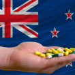 Stock Photo: Holding pills in hand in front of new zealand national flag