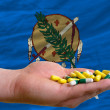 Holding pills in hand in front of oklahoma us state flag - Stockfoto