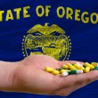 Stock Photo: Holding pills in hand in front of oregon us state flag