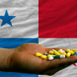 Holding pills in hand in front of panama national flag - Stockfoto