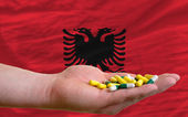 Holding pills in hand in front of albania national flag — Stock Photo