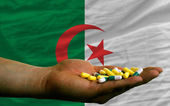 Holding pills in hand in front of algeria national flag — Stock Photo