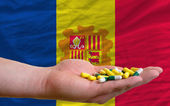 Holding pills in hand in front of andorra national flag — Stock Photo