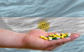 Holding pills in hand in front of argentina national flag — Stock Photo
