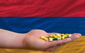 Holding pills in hand in front of armenia national flag — Stock Photo