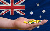Holding pills in hand in front of australia national flag — Stock Photo
