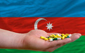Holding pills in hand in front of azerbaijan national flag — Stock Photo