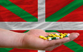 Holding pills in hand in front of basque national flag — Stock Photo