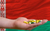 Holding pills in hand in front of belarus national flag — Stock Photo