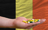Holding pills in hand in front of belgium national flag — Stock Photo