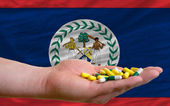 Holding pills in hand in front of belize national flag — Stock Photo