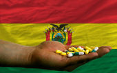 Holding pills in hand in front of bolivia national flag — Stock Photo