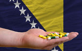 Holding pills in hand in front of bosnia herzegovina national fl — Stock Photo