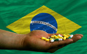 Holding pills in hand in front of brazil national flag — Stock Photo
