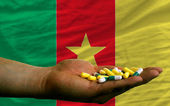 Holding pills in hand in front of cameroon national flag — Stock Photo