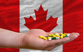 Holding pills in hand in front of canada national flag — Stock Photo