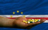 Holding pills in hand in front of capeverde national flag — Stock Photo