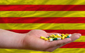Holding pills in hand in front of catalonia national flag — Stock Photo