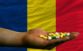 Holding pills in hand in front of chad national flag — Stock Photo