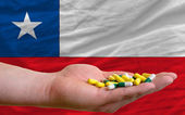Holding pills in hand in front of chile national flag — Stock Photo